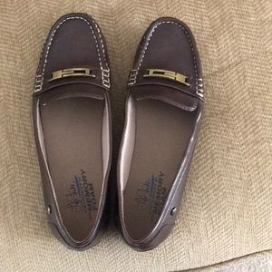 Brown flats with a buckle, loafer  style.
